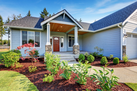 Light blue siding house . Porch with stone base columns and concrete walkway. Northwest, USA Stock Photo