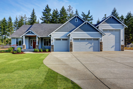 Luxury blue house with curb appeal. Three car garage and long, wide asphalt driveway. Northwest, USA Stock Photo
