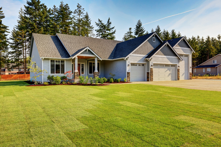 front view: Luxury blue house with curb appeal. Three car garage with driveway . And freshly mowed garden lawn. Northwest, USA Stock Photo