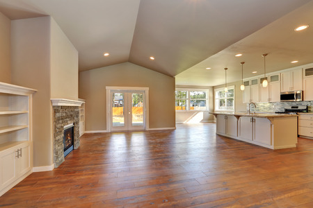 open floor plan: Open plan living room interior with lots of space. Kitchen room view. Vaulted ceiling and hardwood floor. Northwest, USA Stock Photo