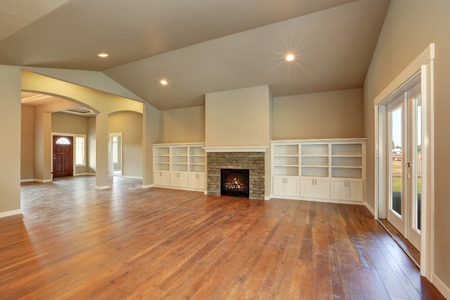 Spacious empty living room interior with vaulted ceiling, built-in storage combination and fireplace with stone trim. Northwest, USA