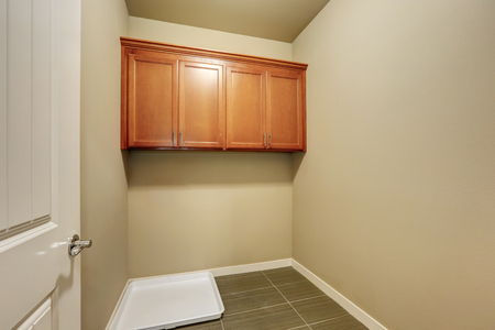 laundry room: Empty beige laundry room with tile floor and cabinets. Northwest, USA Stock Photo