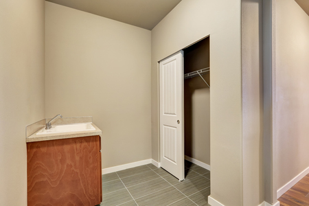 laundry room: Empty beige laundry room with tile floor, sink and closet. Northwest, USA