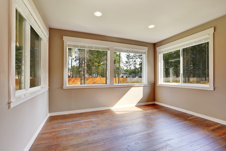 house windows: Brand new house construction interior. Beige Empty room with hardwood floor and windows. Northwest, USA