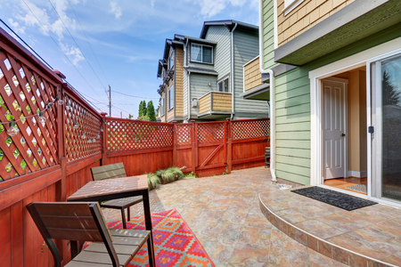 tile flooring: Backyard area with red fence and tile flooring. Northwest, USA