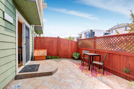 tile flooring: Backyard area with red fence and tile flooring. Duplex house exterior. Northwest, USA Stock Photo