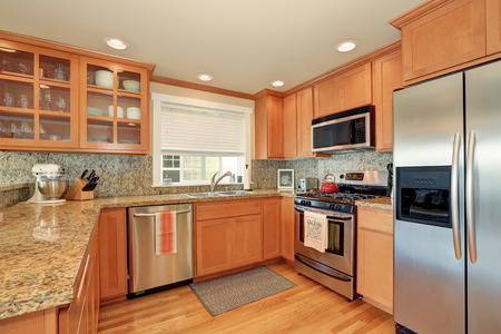 Bright wooden kitchen interior with steel appliances and granite counter top. Northwest, USA Stock Photo