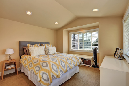 vaulted ceiling: Vaulted ceiling bedroom interior in beige colors. Queen size bed with headboard and yellow blanket. Northwest, USA Stock Photo