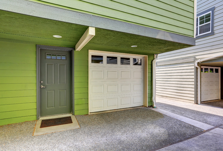 garage on house: Small entrance porch and garage door of green duplex house. Northwest, USA