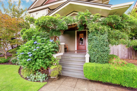 front house: Cozy covered porch sinking in green bushes and trees. Northwest, USA Stock Photo