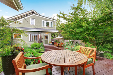 guest house: Back deck of guest house with wooden table set. Luxury house exterior. Northwest, USA