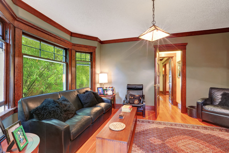floor rug: Traditional living room interior with black leather sofa set, hardwood floor, rug and large window with brown wooden trim. Northwest, USA Stock Photo