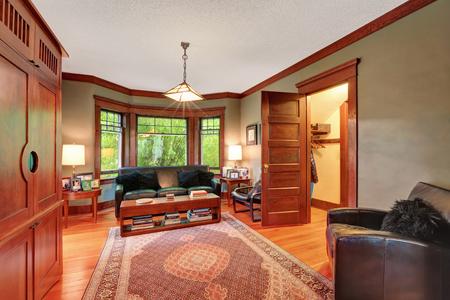 Traditional living room interior with black leather sofa set, hardwood floor, rug and large window with brown wooden trim. Northwest, USA Reklamní fotografie