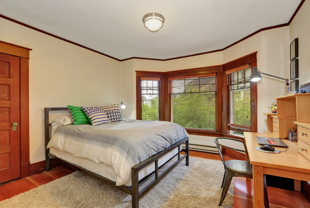 king size bed: White and brown bedroom interior. Furnished with king size bed and wooden desk. Northwest, USA