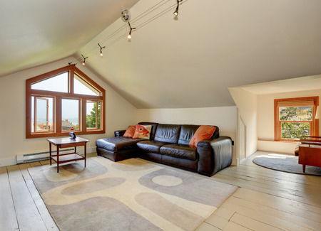 sitting area: Lovely sitting area upstairs. Has vaulted ceiling and black leather sofa. Northwest, USA Stock Photo