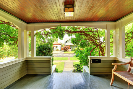 Cozy covered porch interior with wooden bench and white columns. Northwest, USA