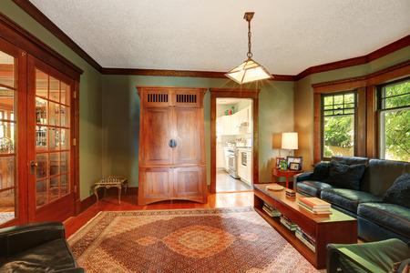 floor rug: Traditional living room interior with black leather sofa set, hardwood floor, rug and antique cabinet. Northwest, USA