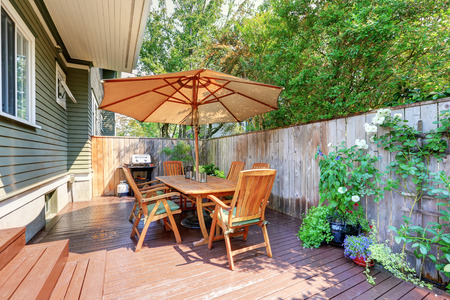 Small wooden walkout deck and patio table set with umbrella. Northwest, USA