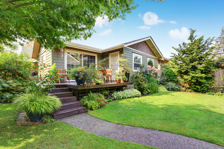 northwest: Backyard area with nicely trimmed garden. Wooden deck with stairs and flower pots. Northwest, USA