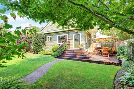 Achtertuin gebied met een staking dek, patio tafel set en goed onderhouden gazon. Northwest, USA Stockfoto