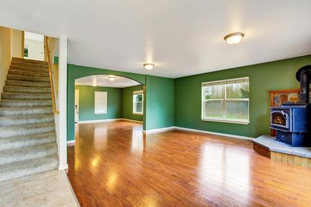 Open floor plan interior with green walls, fireplace and hardwood floor. . Northwes, USA Stock Photo