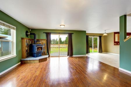 open floor plan: Open floor plan interior with green walls, brown curtains, fireplace and hardwood floor. . Northwes, USA