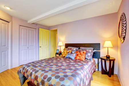 Bedroom interior in purple tones with wardrobe and deep brown wooden furniture. Northwest, USA