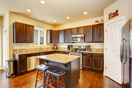 Kitchen room interior with deep brown cabinets, hardwood floor and island. Northwest, USA Stock Photo