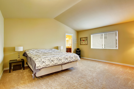 Spacious bedroom interior in beige tones and carpen floor. Northwest, USA