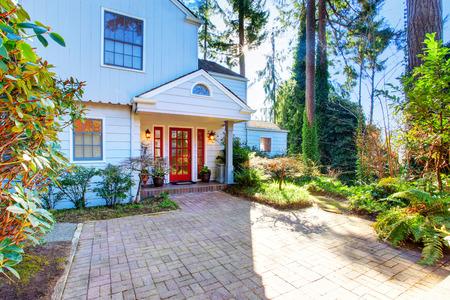 portada: Exterior de la casa con la puerta frontal de color rojo y de la pasarela de baldosas. Noroeste, EE.UU. Foto de archivo