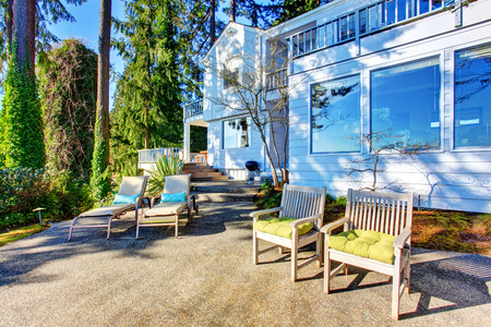 Backyard patio area with chairs, concrete walkway and nice landscaping desing. Northwest, USA Stock Photo