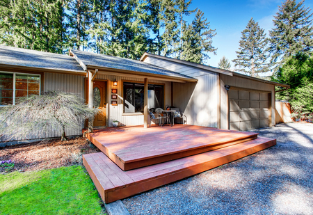 grey house: Grey house with wooden trim and gravel walkway. View of entrance column porch. Northwest, USA