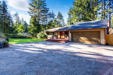 grey house: Grey house with wooden trim, garage and gravel walkway. View of entrance column porch. Northwest, USA Stock Photo