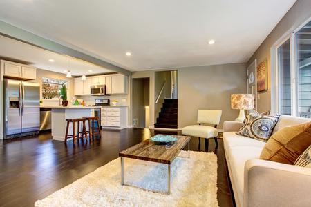 Open floor plan. Cozy living room interior with hardwood floor connected to kitchen. Northwest, USA