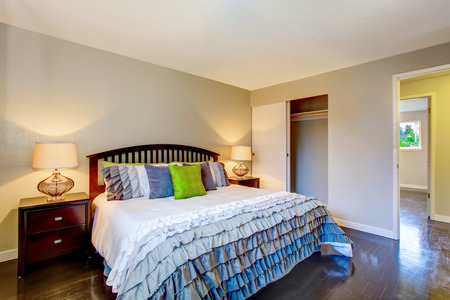king size bed: Bedroom interior with beige walls, deep brown hardwood floor and king size bed. Northwest, USA