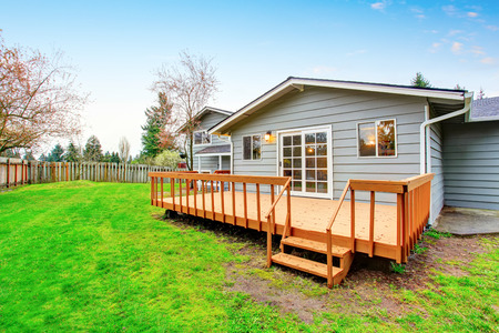 garden styles: Two story house with wooden walkout deck. Fenced backyard. Northwest, USA