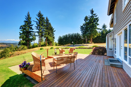 deck: Large walkout deck with wicker furniture and perfect  landscape view. Northwest, USA Stock Photo