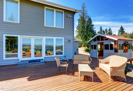 house windows: Large walkout deck with wicker furniture and barbecue shed. Northwest, USA
