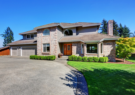 curb: Luxury Brick house with beautiful curb appeal with perfectly trimmed front lawn. Northwest, USA Stock Photo