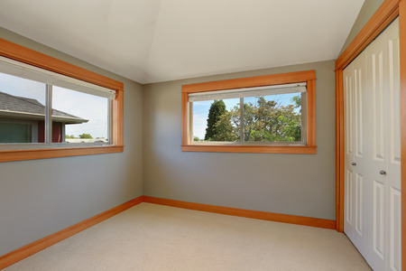 remodeled: Grey interior of empty room with two windows and white doors closet. Northwest, USA Stock Photo