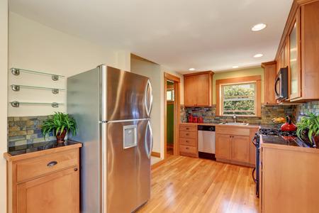 fridge: Light brown kitchen cabinetry, brick tile back splash trim and stainless steel fridge. Kitchen interior. Northwest, USA