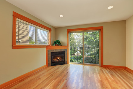polished floor: Empty living room with corner fireplace and polished hardwood floor. Northwest, USA Stock Photo