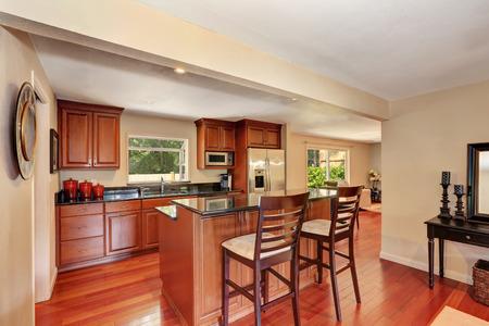 Wooden kitchen interior with kitchen island and stainless steel fridge. Northwest, USA