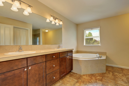 corner tub: Great bathroom interior with corner bath tub, marble floor, vanity cabinet with two sinks and large mirror. Northwest, USA