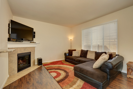 brown leather sofa: Family room interior. Corner fireplace with tile trim and TV, brown leather sofa with pillows and colorful rug. Northwest, USA Stock Photo
