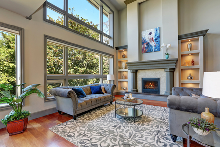 family rooms: Grey interior of high vaulted ceiling family room in luxury house with fireplace and large windows. Northwest, USA.