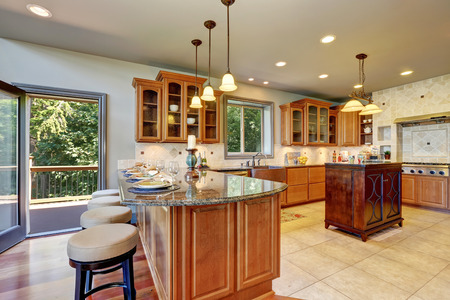 cabinets: Luxury kitchen room interior with cabinets and granite counter tops. Bar counter with elegant pendant lights and dinner setting. Open door to the balcony. Northwest, USA