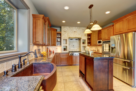 granite wall: Great kitchen interior with large steel fridge and kitchen island. Also tile wall trim and granite counter tops. Northwest, USA