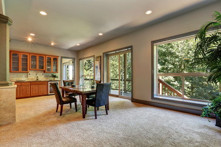 Open floor plan dining room with view of kitchen cabinetry. Beige carpet floor and opened glass sliding doors to balcony. Northwest, USA