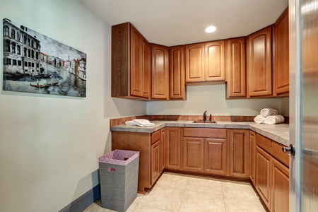 laundry room: Laundry room with sink and wood cabinets. New luxury home interior. Northwest, USA Stock Photo